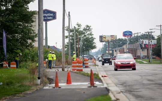 Construction crews work on building pedestrian footpaths along West Fox Ridge Lane. The project is also adding more sidewalks and pedestrian crossings in the area.