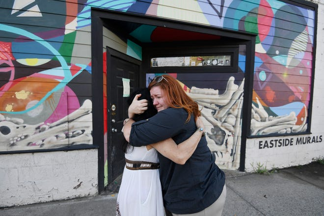 Julie Ewell hugs an employee outside The Cobra bar Monday, Aug. 20, 2018, where two victims were killed as part of a string of shootings that have terrorized Nashville this month.