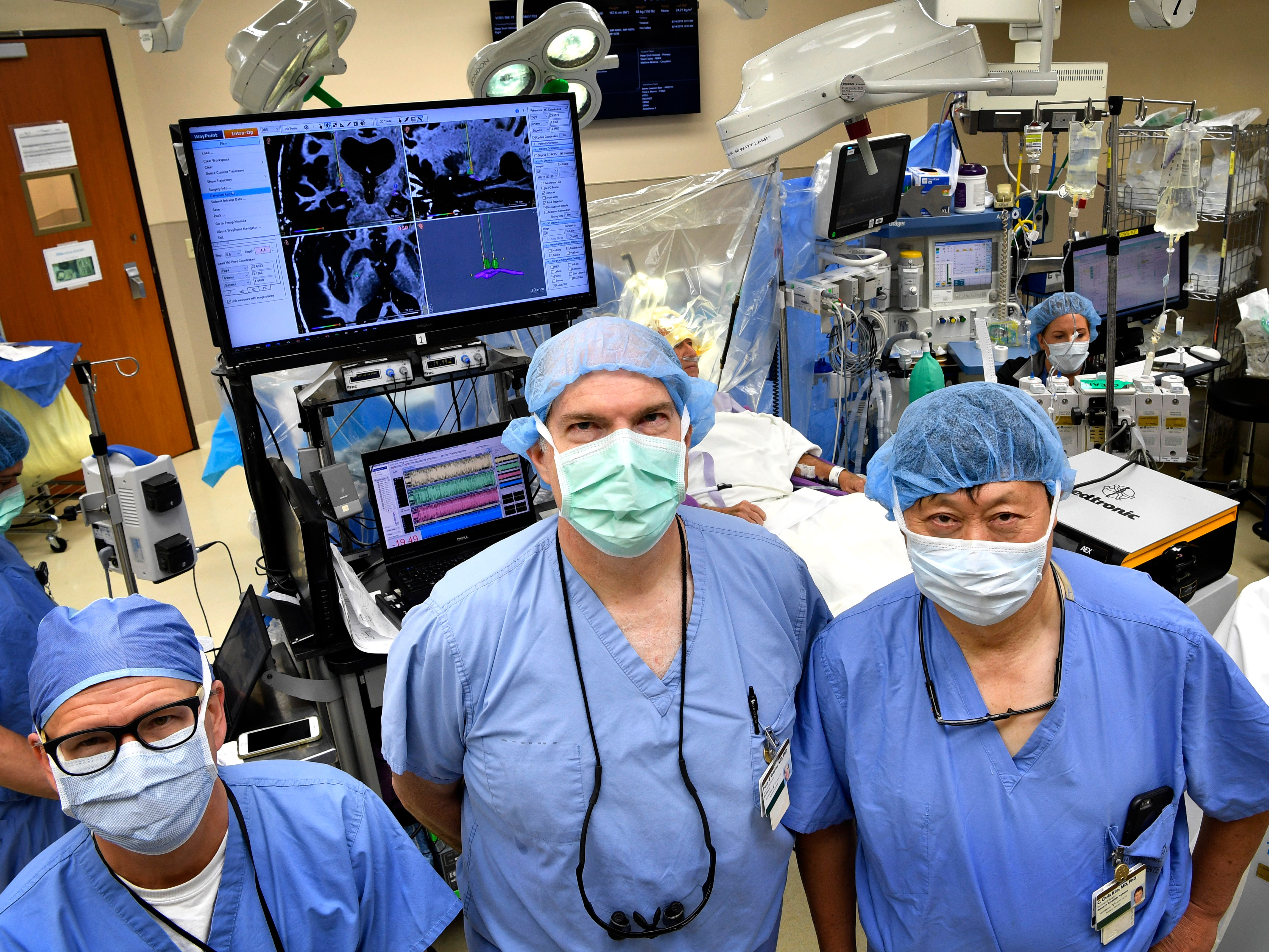 From left, neurologist Dr. Tom Davis, neurosurgeon Dr. Peter Konrad, and  neurophysiologist Dr. C. Chris Kao, pose for a photo inside the operating room after performing a Deep Brain Stimulation surgery at Vanderbilt University Medical Center on Tuesday Aug. 14, 2018.
