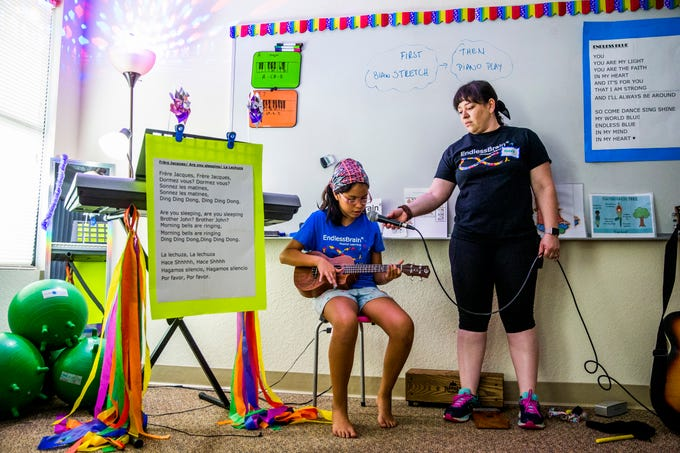 Mabel Diaz holds the microphone for Camila Chang, 11, as she sings during the EndlessBrain summer camp at Emmanuel Lutheran Church in Naples on Thursday, Aug. 9, 2018.