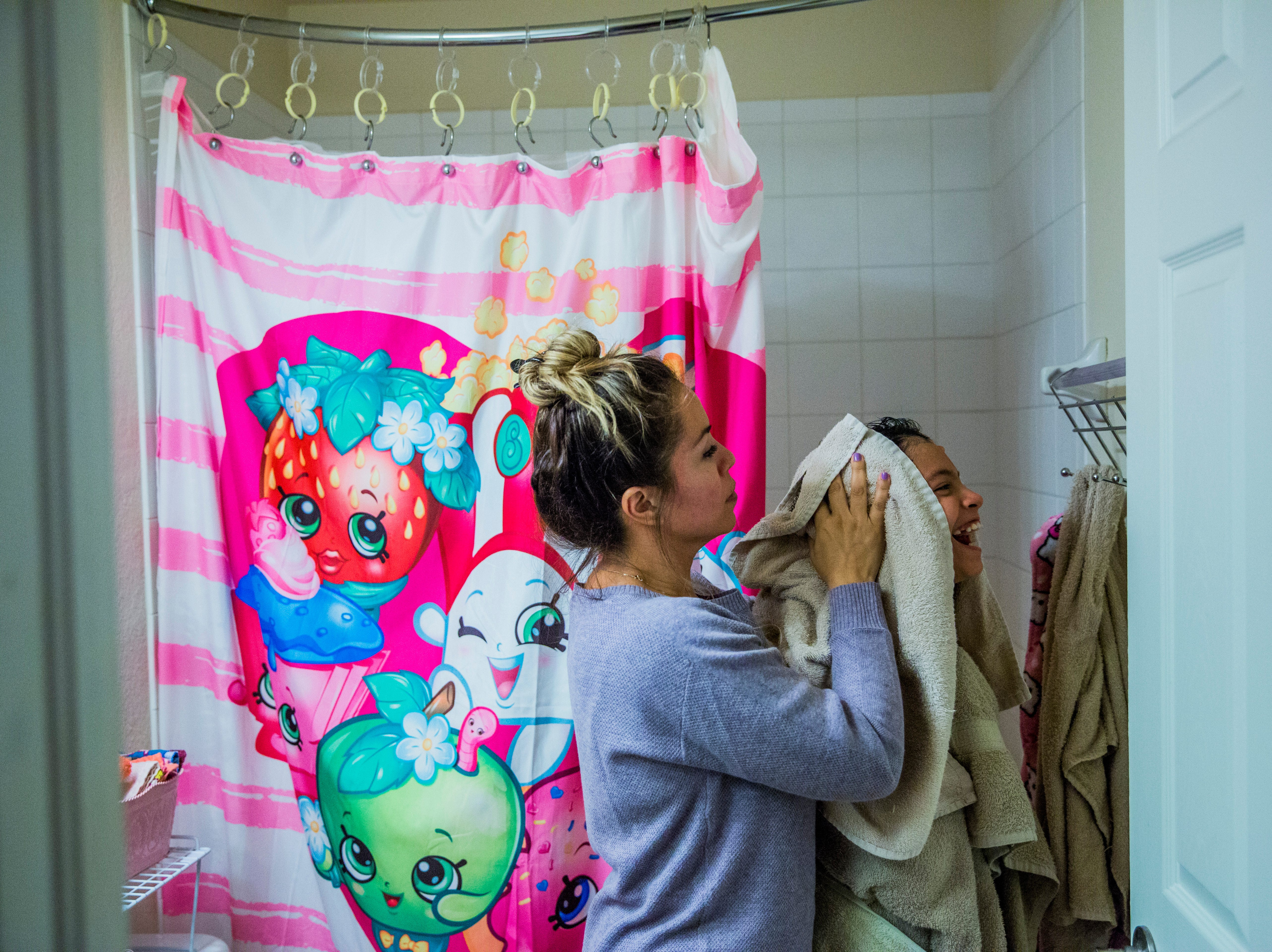 Marcela Guimoye helps dry off her daughter Camila Chang, 11, after a shower during their nighty routine in their North Naples home on Tuesday, Aug. 14, 2018.