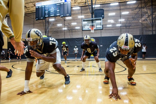 The defensive line runs drills during football practice at Golden Gate High School on Monday, August 20, 2018.