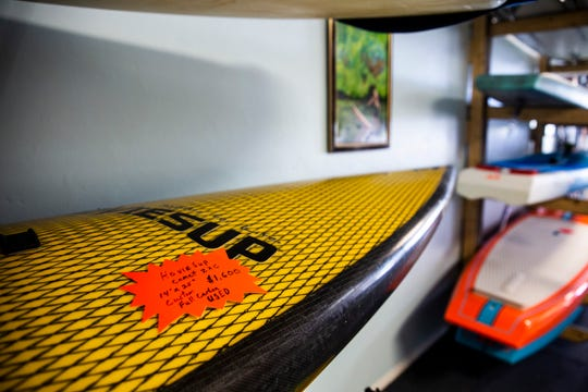 A used paddleboard sits on a shelf for sale at CGT Kayaks in Bonita Springs on Monday, August 20, 2018. The sale of paddleboards and kayaks has drastically slowed due to the pervasiveness of red tide along the coast.