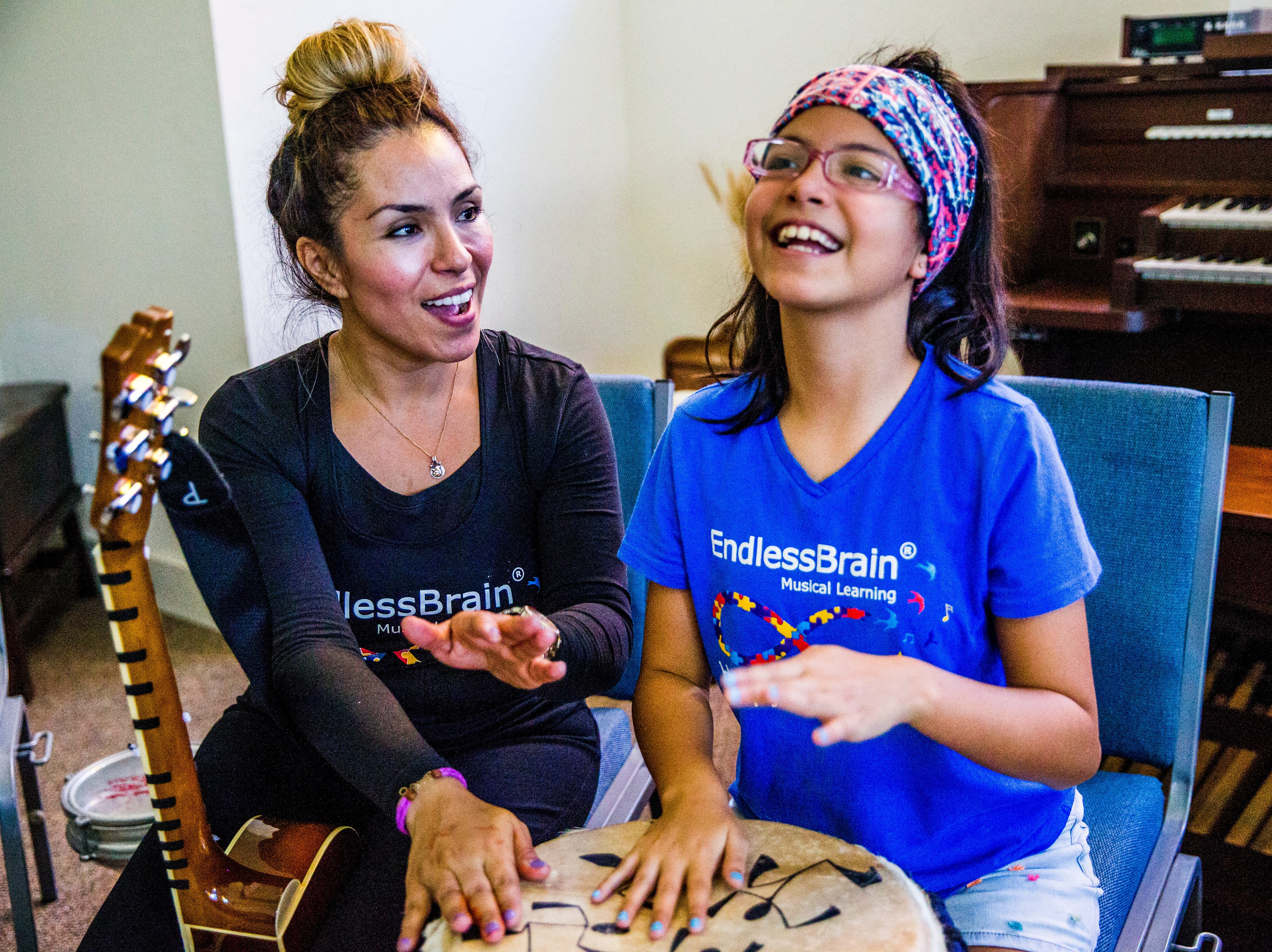 Marcela Guimoye and her daughter Camila Chang, 11, drum together during a drum circle at the EndlessBrain summer camp at Emmanuel Lutheran Church in Naples on Thursday, Aug. 9, 2018.