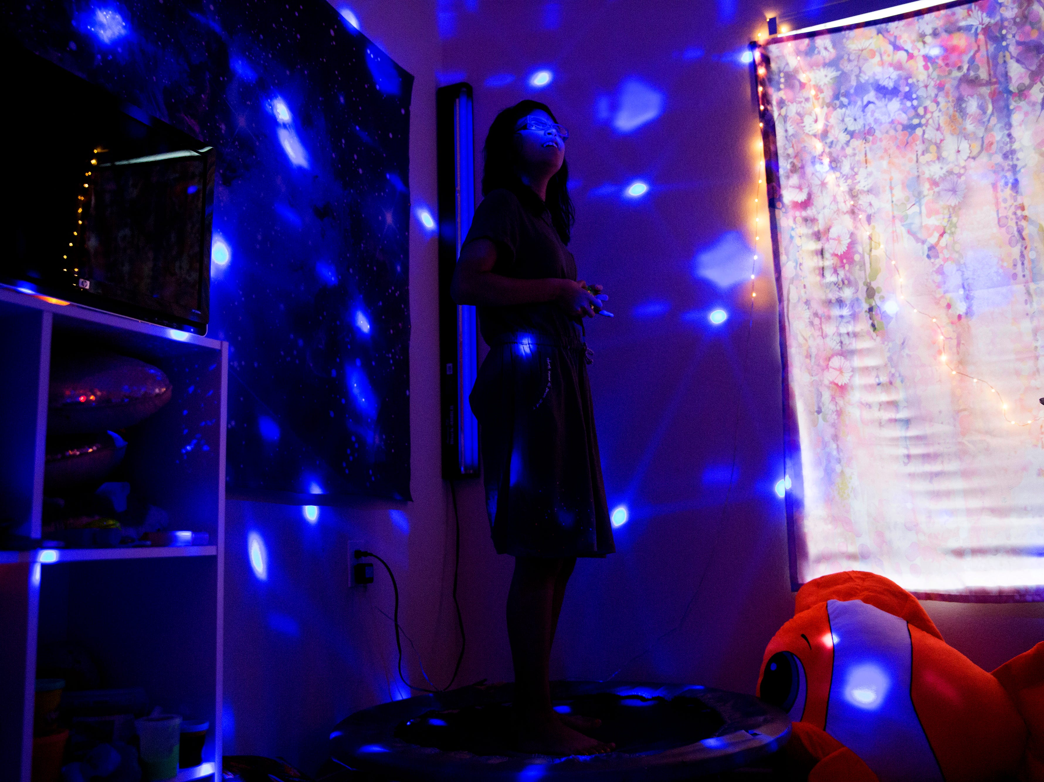 """Camila Chang, 11, listens to music in her """"sensory room"""" in her North Naples home on Tuesday, Aug. 14, 2018. Camila was diagnosed with autism when she was two and a half years old and goes to her """"sensory room"""" to immerse herself in music. Because of Camila's love for music and the lack of services for kids with autism in Southwest Florida, Camila's mother Marcela Guimoye started a nonprofit called EndlessBrain. EndlessBrain provides music opportunities for kids with special needs. """"My expectations for EndlessBrain is to make Camila as happy as possible and give kids like her the same opportunity,"""" Guimoye says."""