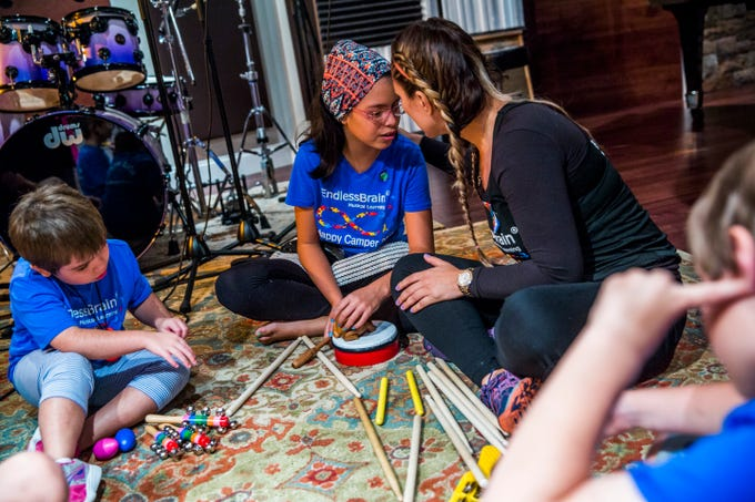 "Marcela Guimoye and her daughter Camila Chang, 11, share a moment together at Mastertrax Recording Studio during the EndlessBrain summer camp in Bonita Springs on Tuesday, Aug. 7, 2018. ""It's (endless brain) all her. It's always been her,"" Guimoye says of her daughter."