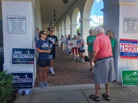 A library patron prepares to run the gantlet of campaigners greeting early voters at the Collier County Library headquarters on Orange Blossom Drive on Monday, Aug. 20, 2018.