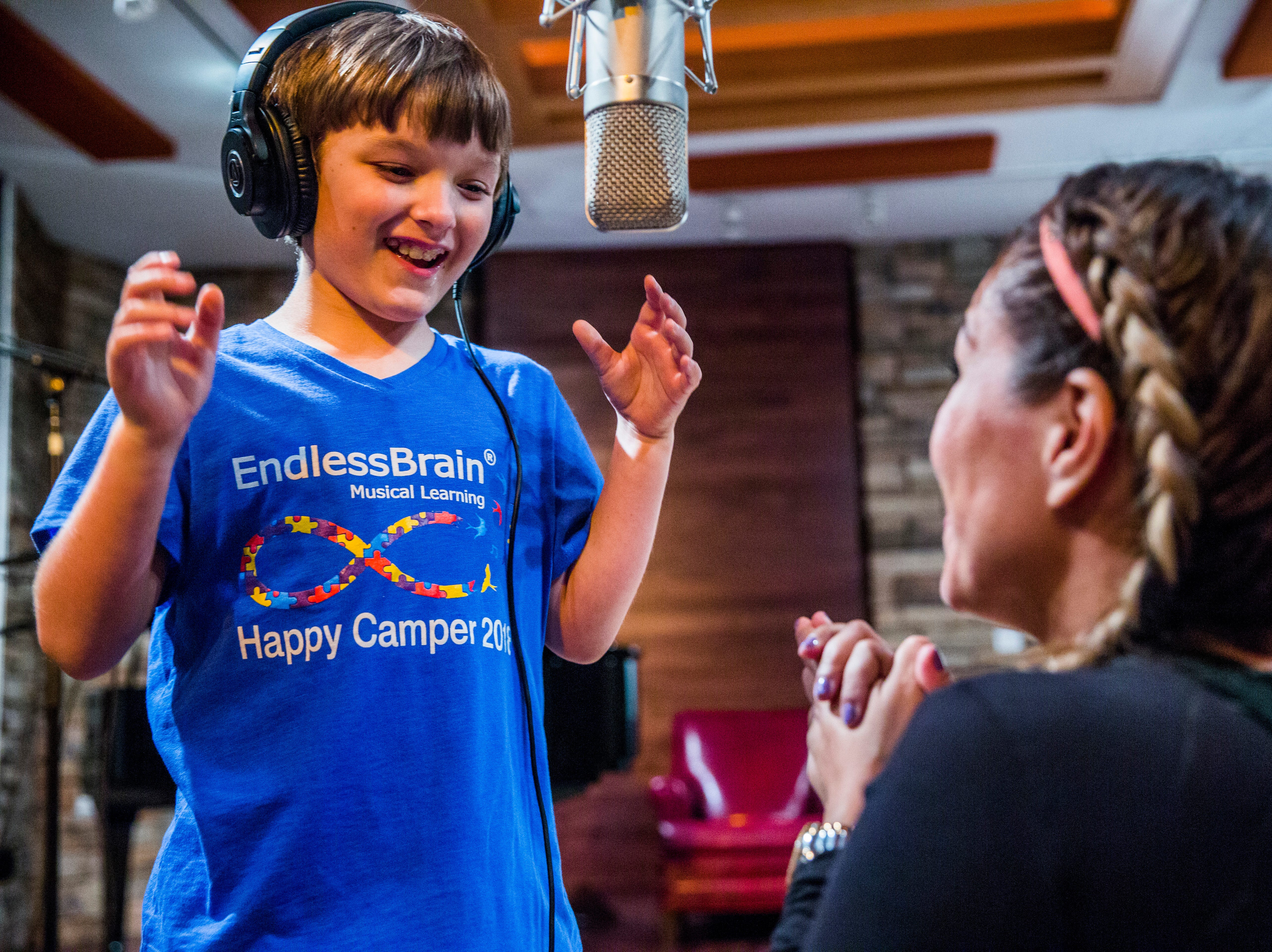 Marcela Guimoye encourages Harry Conroy, 10, as he sings at Mastertrax Recording Studio in Bonita Springs on Tuesday, Aug. 7, 2018. Guimoye put together a CD of the songs that the kids learned during the EndlessBrain summer camp.