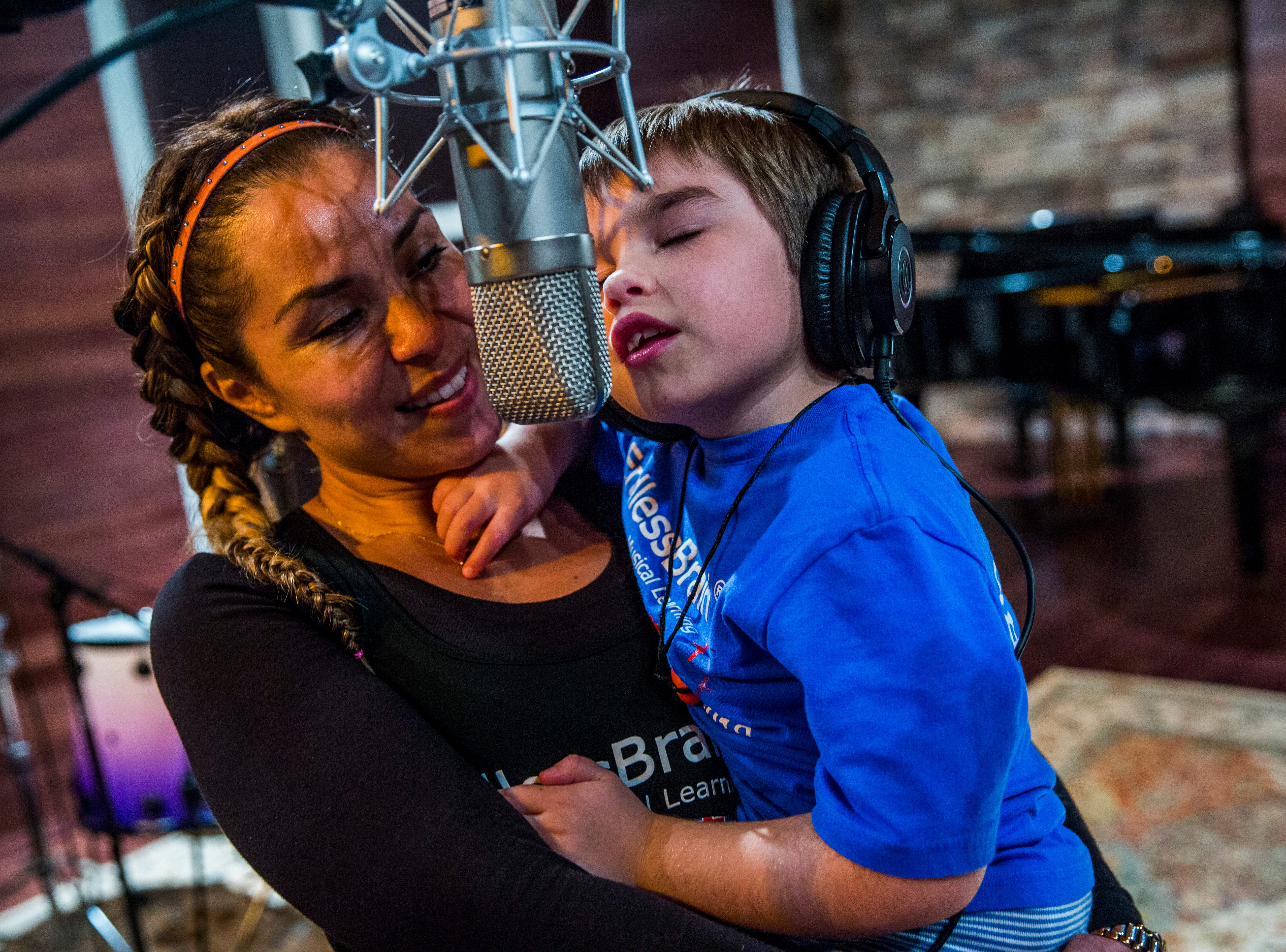 Marcela Guimoye holds Talley Louise Wilson, 7, as she sings at Mastertrax Recording Studio in Bonita Springs on Tuesday, Aug. 7, 2018. Before becoming involved with EndlessBrain, Talley didn't verbally communicate much, but her parents say she can communicate clearer and she sings much more.