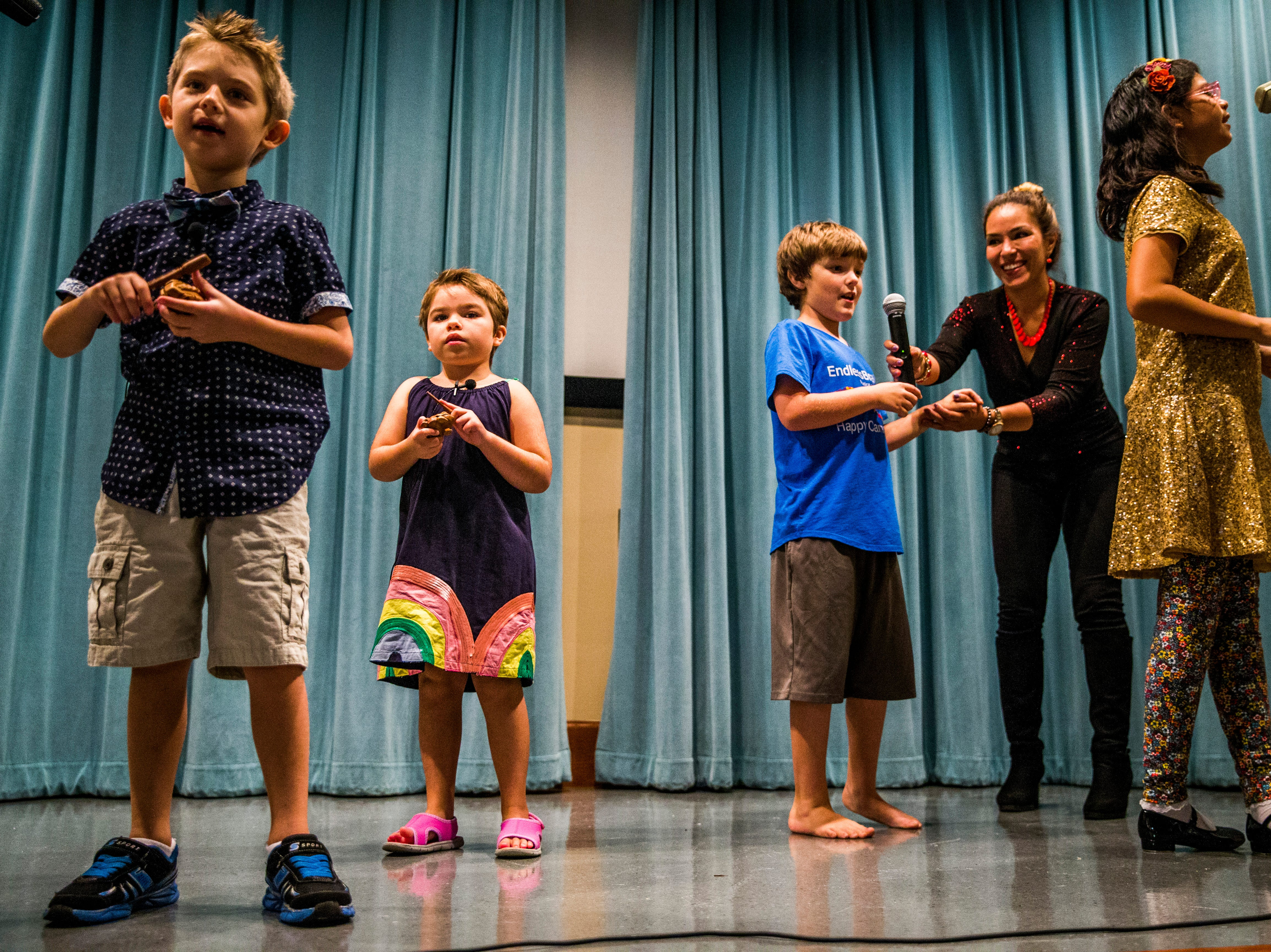"""EndlessBrain campers sing during a recital for their friends and family with the help of Marcela Guimoye at the Collier County Library in Naples on Saturday, Aug. 11, 2018. """"This is a place for parents to feel like their kids with special needs are safe and know that their kids are loved,"""" Guimoye says."""