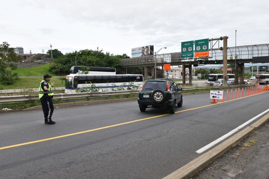 A North Bergen Police Officer directs a vehicle out of the NJ Transit bus only lane, which is to allow buses to merge onto the NJ Turnpike, while all other vehicles are forced to merge onto Route 1&9 north. Construction on the Route 495 bridge to the Lincoln Tunnel has closed the left lane in each direction in North Bergen on Monday August 20, 2018.