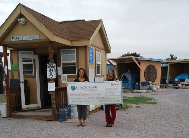 Nicole Martinez, executive director for Mesilla Valley Community of Hope, accepts a check from vice president Rhena Phillips of Citizens Bank.