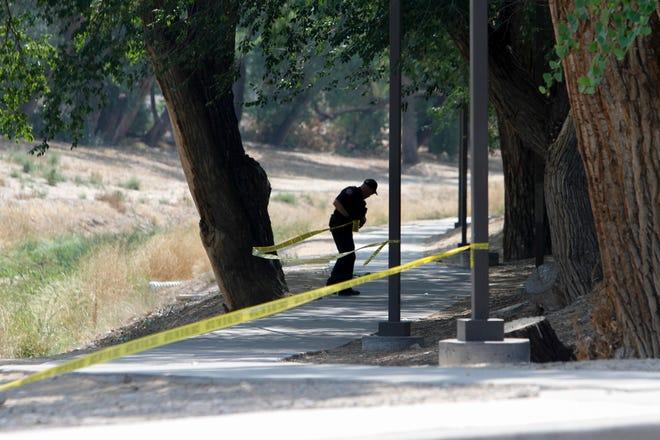 A Farmington police officer secures evidence Monday at Brook Haven Park East on West Apache Street in Farmington.