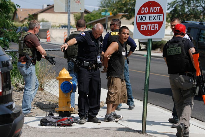 A Farmington police officer secures stabbing suspect Raheem Benally, 24, Monday at Apache Elementary School in Farmington.