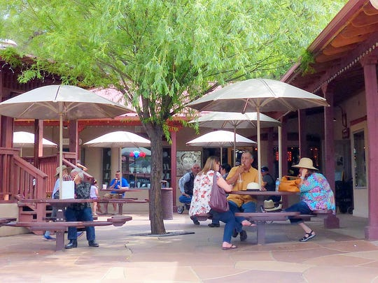Shoppers enjoy some snacks in the cool courtyard of Times Square on Sudderth Drive in Midtown Ruidoso.