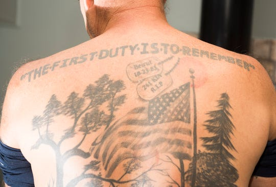 Navy veteran Ed Brownshows one of the tattoos he has to honor his comrades killed the 1983 Beirut barracks bombing.