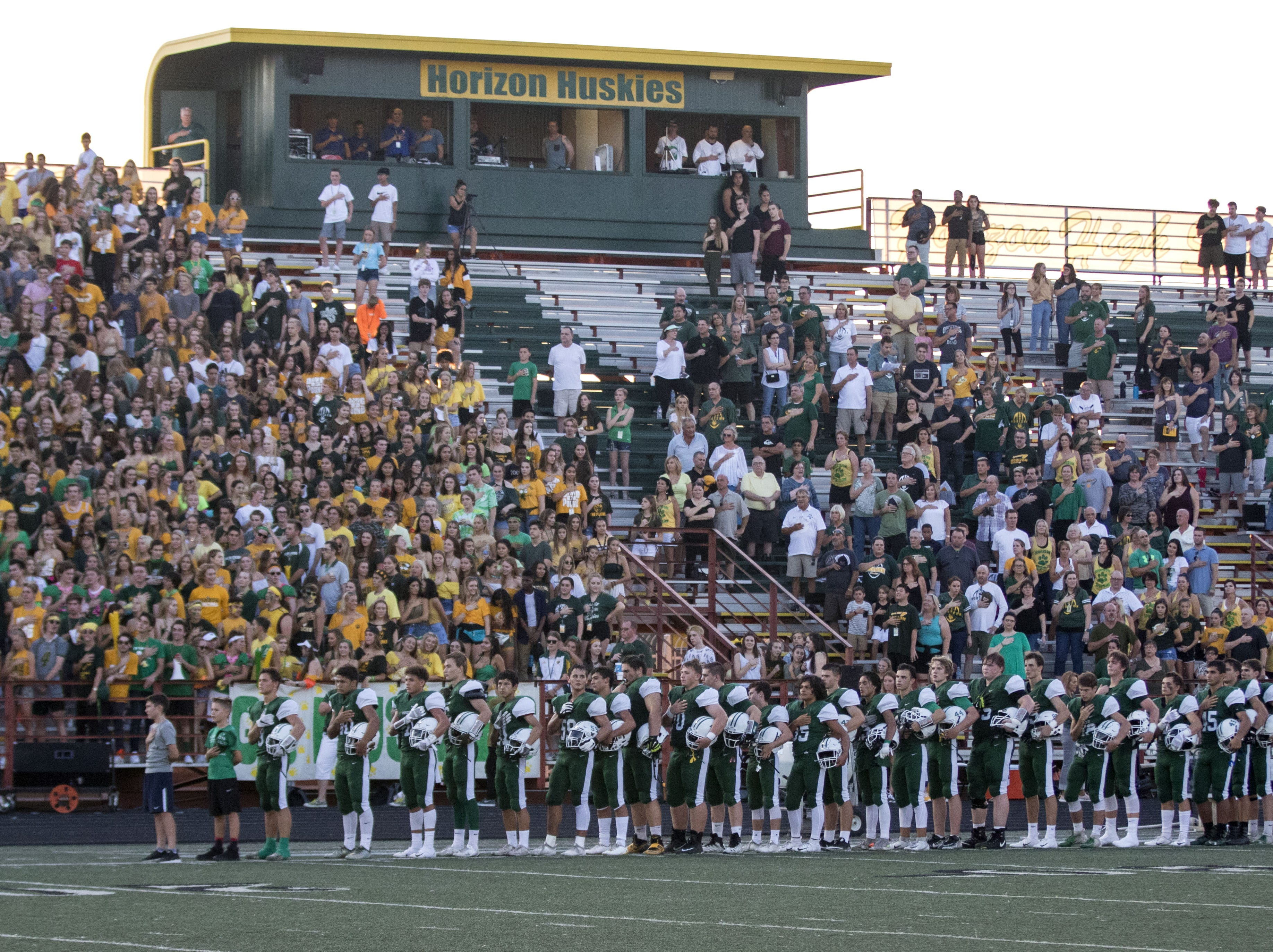 Horizon fans and players stand during the National Anthem before their game with Marana Friday, Aug.17, 2018.