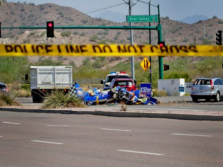 The wreckage of a small plane sits in an intersection, Aug. 20, 2018, in Phoenix. The plane went down near the city's Deer Valley Airport.
