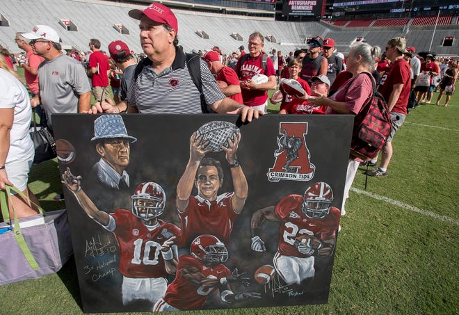 James Marino stands in line to get a painting autographed by Alabama Crimson head coach Nick Saban during the University of Alabama football fan day at Bryant-Denny Stadium on Aug. 4, 2018.