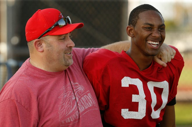 Head football coach Ryan Felker puts his arm around defensive back Gerald Wilbon during practice at Mesa Community College on Aug. 16, 2018. Wilbon is one of 11 junior college football players who have filed a federal lawsuit over the decision to eliminate football in the Maricopa County Community College District.