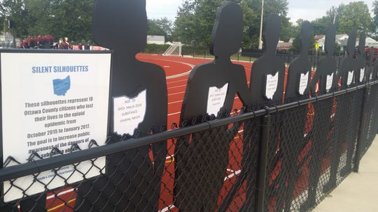 """Some of the """"Silent Silhouettes"""" that represent Ottawa County drug overdose victims lined the fence at a Port Clinton football game last year. The silhouettes are powerful reminders of the dangers of opiate use."""