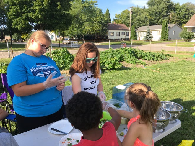 From left, Maureen Deising and Lizzy Schaaf help neighborhood kids make salsa using produce they grew a newly refurbished garden at the Harrison Center on Aug. 13, 2018, in Port Huron.