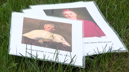 Pictures of Bishop George L. Leech and Bishop Ronald Gainer lay on the grass, as  representatives of SNAP make remarks pushing for change and accountability following leadership failures identified in the PA grand jury report on priest sex abuse.