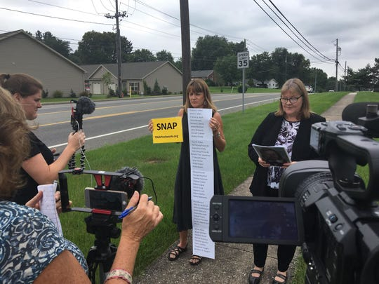 Becky Ianni, right, director of the Washington, DC/Virginia Survivors Network of those Abused by Priests, talks outside the Harrisburg Catholic diocese on Monday pushing for action and reform in the wake of a PA grand jury report on priest abuse.