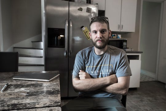 "Jacob Ohlinger sits in the kitchen of A New Life Sober Living in the Landisville area of East Hempfield Township, Lancaster County. Ohlinger, 28, is in recovery from heroin addiction and works as an outreach coordinator for the organization. On Jan. 29, 2017, Spring Garden Township police arrested him on drug possession charges as he was walking down the street. He lost his driver's license for six months. ""I remember making that conscious decision not to get in my vehicle,"" Ohlinger said."