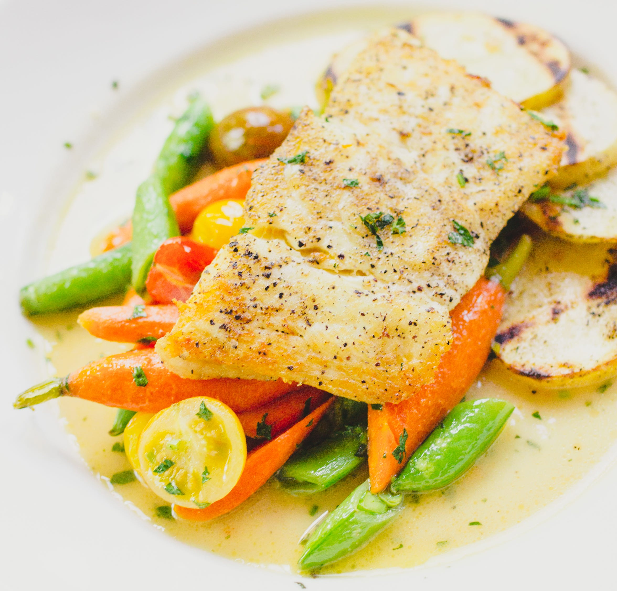 A colorful plating of halibut, baby carrots and snow peas at PlumpJack Cafe, the restaurant in PlumpJack Squaw Valley Inn in Squaw Valley, Calif., on Lake Tahoe's North Shore. The resort takes its name from a Shakespeare character.