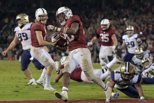 Nov 10, 2017; Stanford, CA, USA; Stanford running back Bryce Love (20) is defended by Washington defensive back Austin Joyner (4) on a 9-yard touchdown run in the fourth quarter during an NCAA football game at Stanford Stadium. Stanford defeated Washington 30-22.