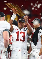 Jan 8, 2018; Atlanta, GA, USA; Alabama Crimson Tide quarterback Tua Tagovailoa (13) celebrates with the trophy after the 2018 CFP national championship college football game against the Georgia Bulldogs at Mercedes-Benz Stadium.