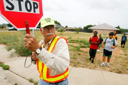 Crossing guard Gerald Cox leads a group of Bowie Elementary School students across Sunset Drive in San Angelo in September 2010.