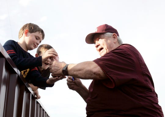 """Howard """"Doc"""" Edwards hands a bobble-head of his own likeness to a young fan before a game in August 2007, when he was finishing his 50th season in professional baseball."""