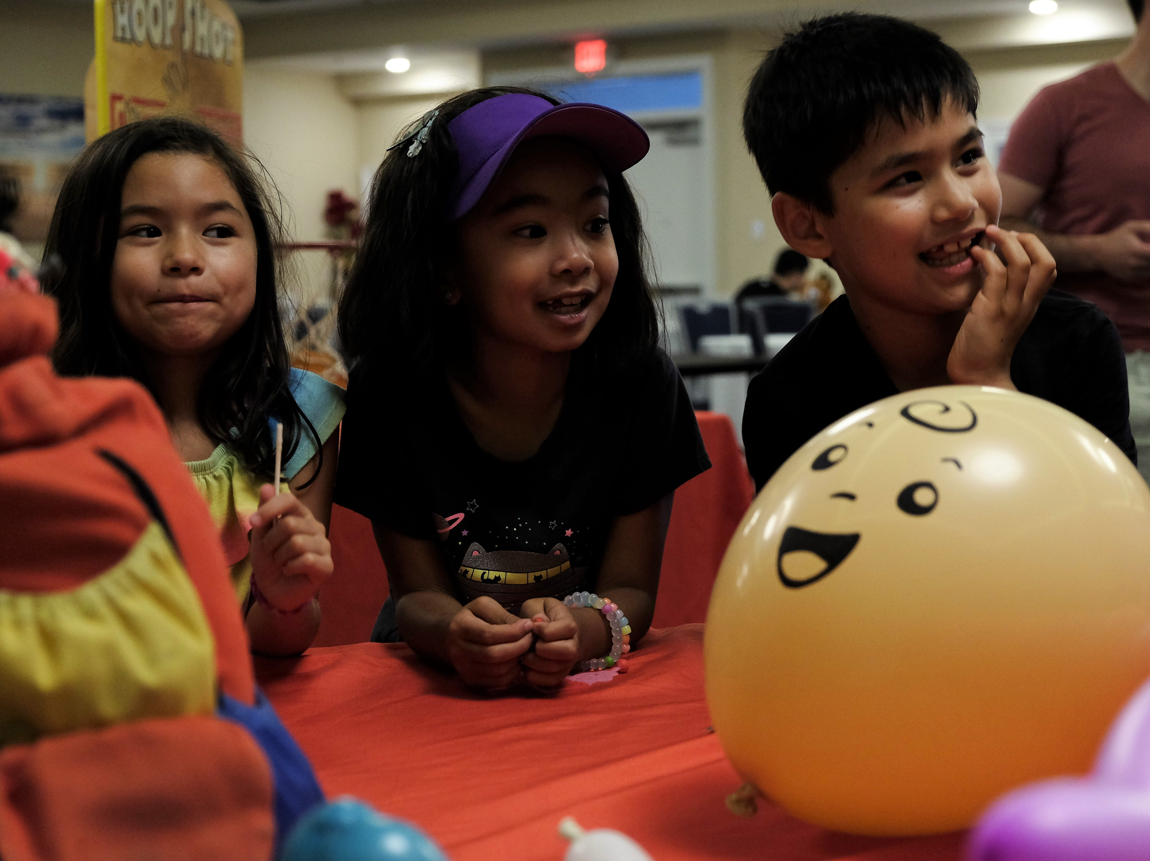Three kids look at the balloons created by Renate McIntosh on Aug. 15 at Bethany Beach Ocean Suites.