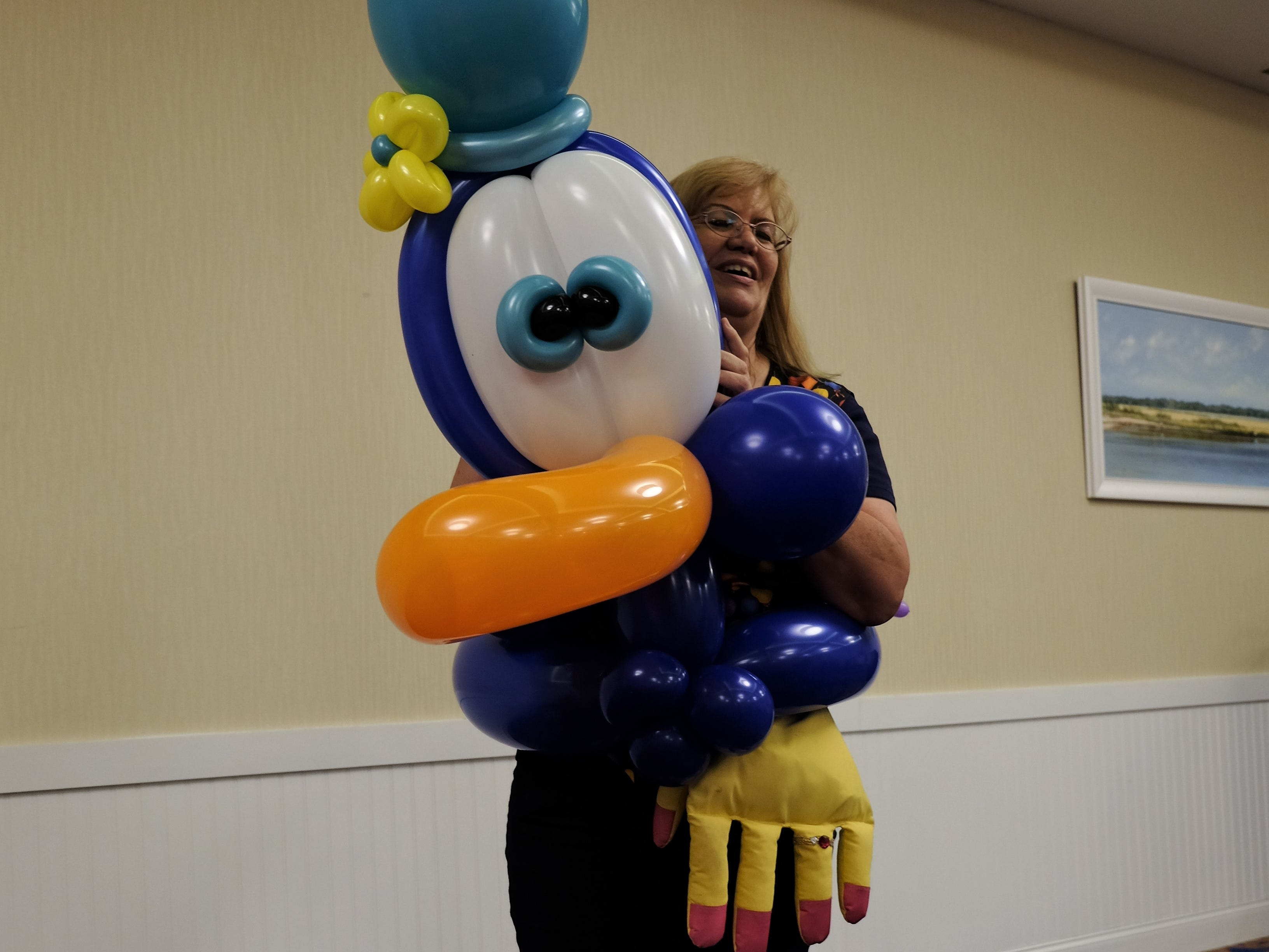 Renate McIntosh, an entertainer, settles into one of her favorite balloon creations on Aug. 15 at Bethany Beach Ocean Suites.