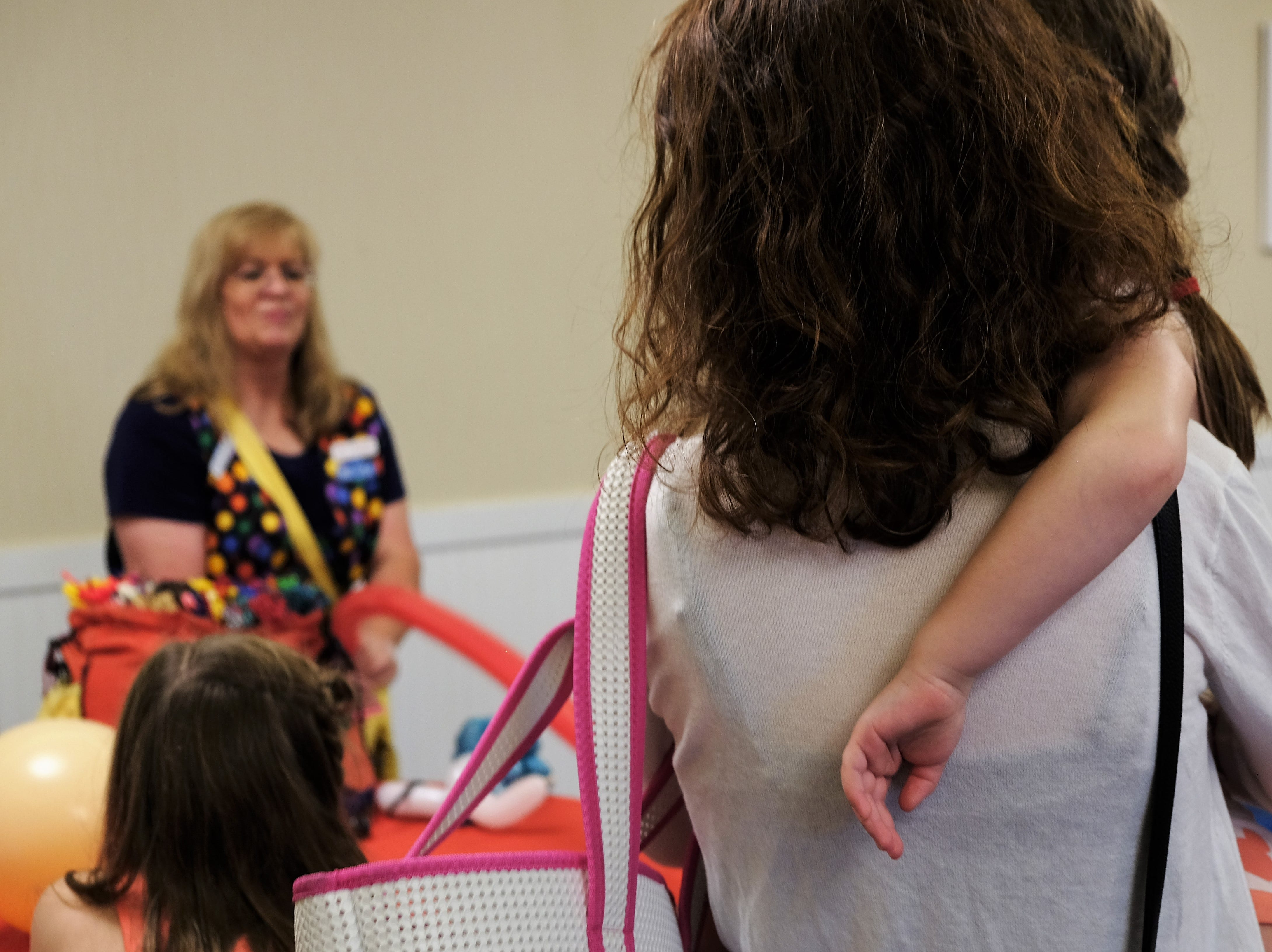 Families watch Renate McIntosh turn balloons into jet packs, dogs and other objects in the realm of existence Aug. 15 at Bethany Beach Ocean Suites.