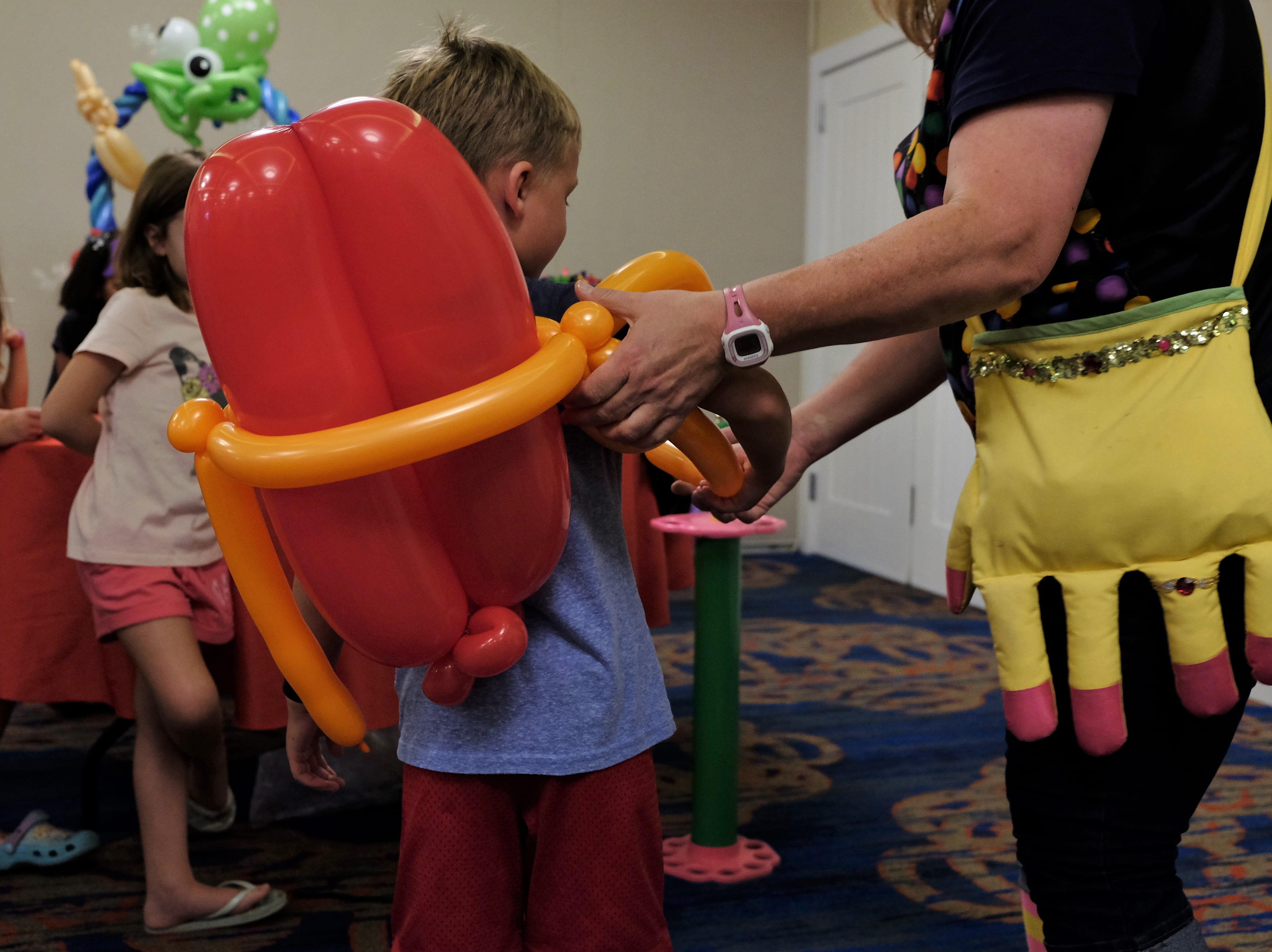 Renate McIntosh, an entertainer, helps a boy into his jet pack on Aug. 15 at Bethany Beach Ocean Suites.