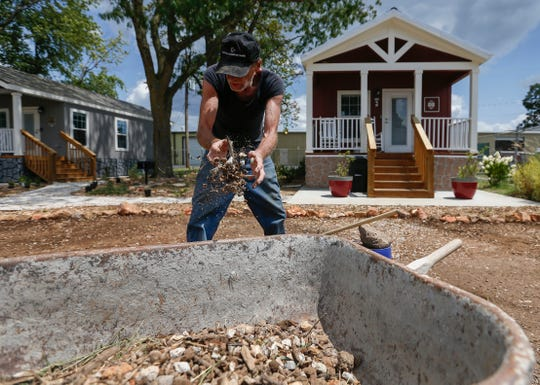 Tommy Yarberry tosses some gravel into a wheelbarrow in his future front yard at Eden Village on Monday, Aug. 6, 2018. Yarberry, who has been homeless for three years, will be the first resident to move into the new community.