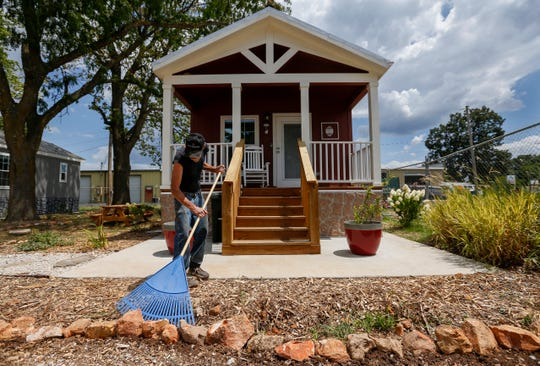 Tommy Yarberry rakes the mulch in his future front yard at Eden Village on Monday, Aug. 6, 2018. Yarberry, who has been homeless for three years, will be the first resident to move into the new community.