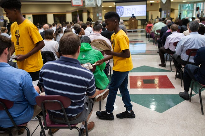 Two boys hand out information about Sunday's ceremony at Central High School honoring civil rights icon and Springfield resident Rev. Oliver Brown.