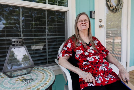 Nancy Lawrence smiles as she sits on the front porch of her future home at Eden Village on Thursday, Aug. 16, 2018. Lawrence, who is deaf and lived in her car for years, will be the second person to move into the new community.