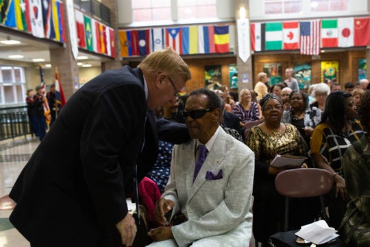 Mayor Ken McClure talks with former councilman Denny Whayne at Sunday's celebration of Rev. Oliver Brown at Central High School.