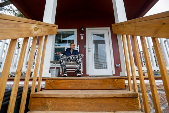 Tommy Yarberry smokes a cigarette while relaxing in a rocking chair on his future front porch at Eden Village on Tuesday, Aug. 14, 2018. Yarberry, who has been homeless for three years, will be the first resident to move into the community.