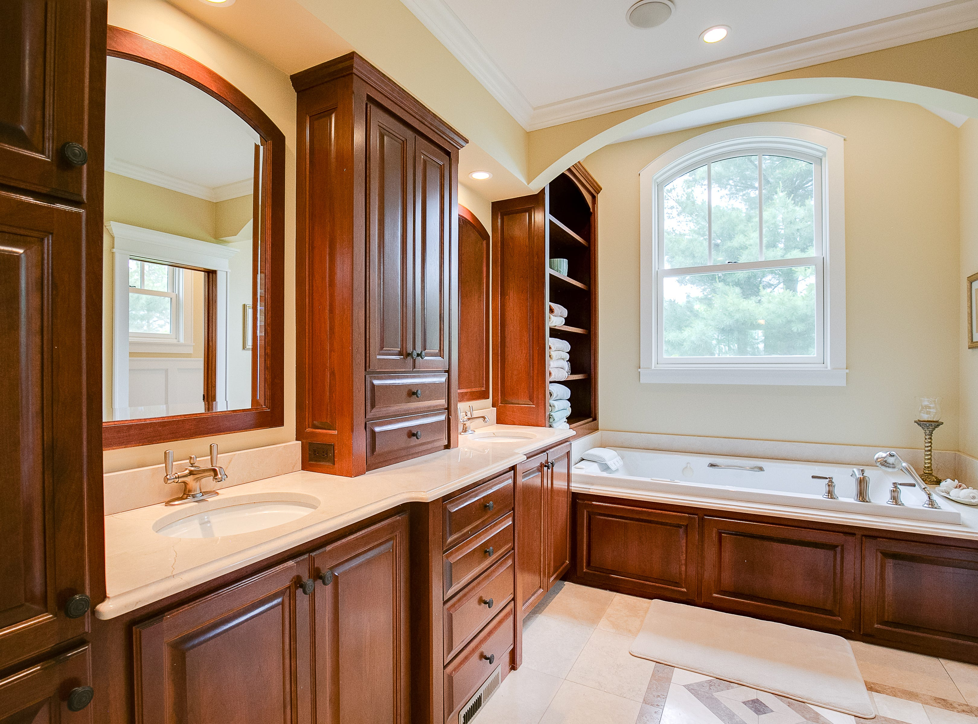 The master bath is resplendent with marble vanities and cherry built cabinetry, as well as a jetted tub and radiant floor heat.