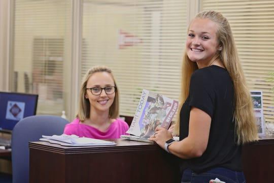 Olivia Dickey of North Florida Community College's Enrollment Services department helps high school dual enrollment student Summer Roberts get ready for fall classes at NFCC.