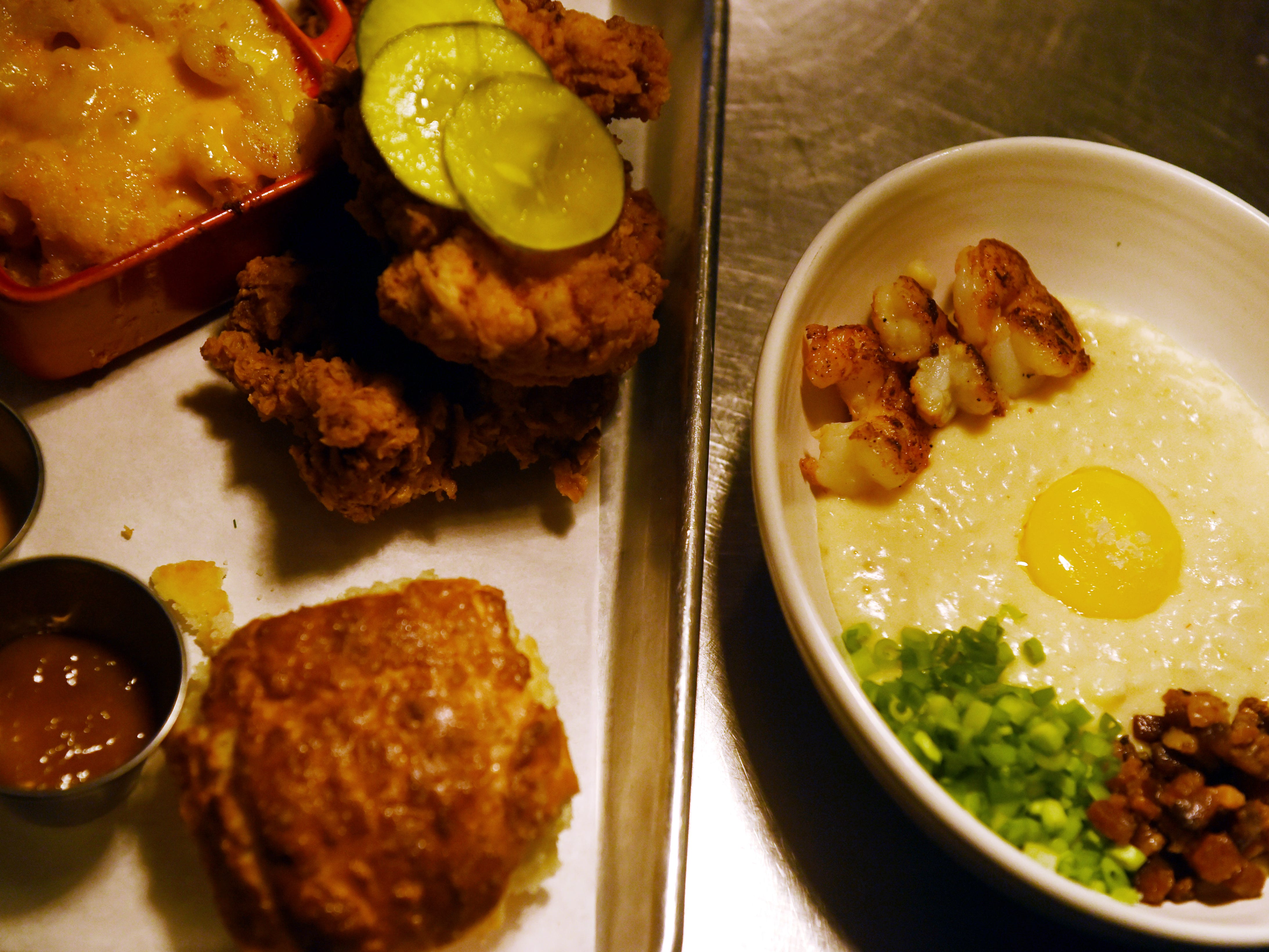 """Sweet tea fried chicken, buttermilk biscuit and jam, best """"GD"""" mac and cheese, crack sauce and pickles (left) and blackened Gulf shrimp, Anson Mills grits, pimento cheese, slab bacon, green onion and poached egg yolk at District Table & Bar in Port Salerno."""