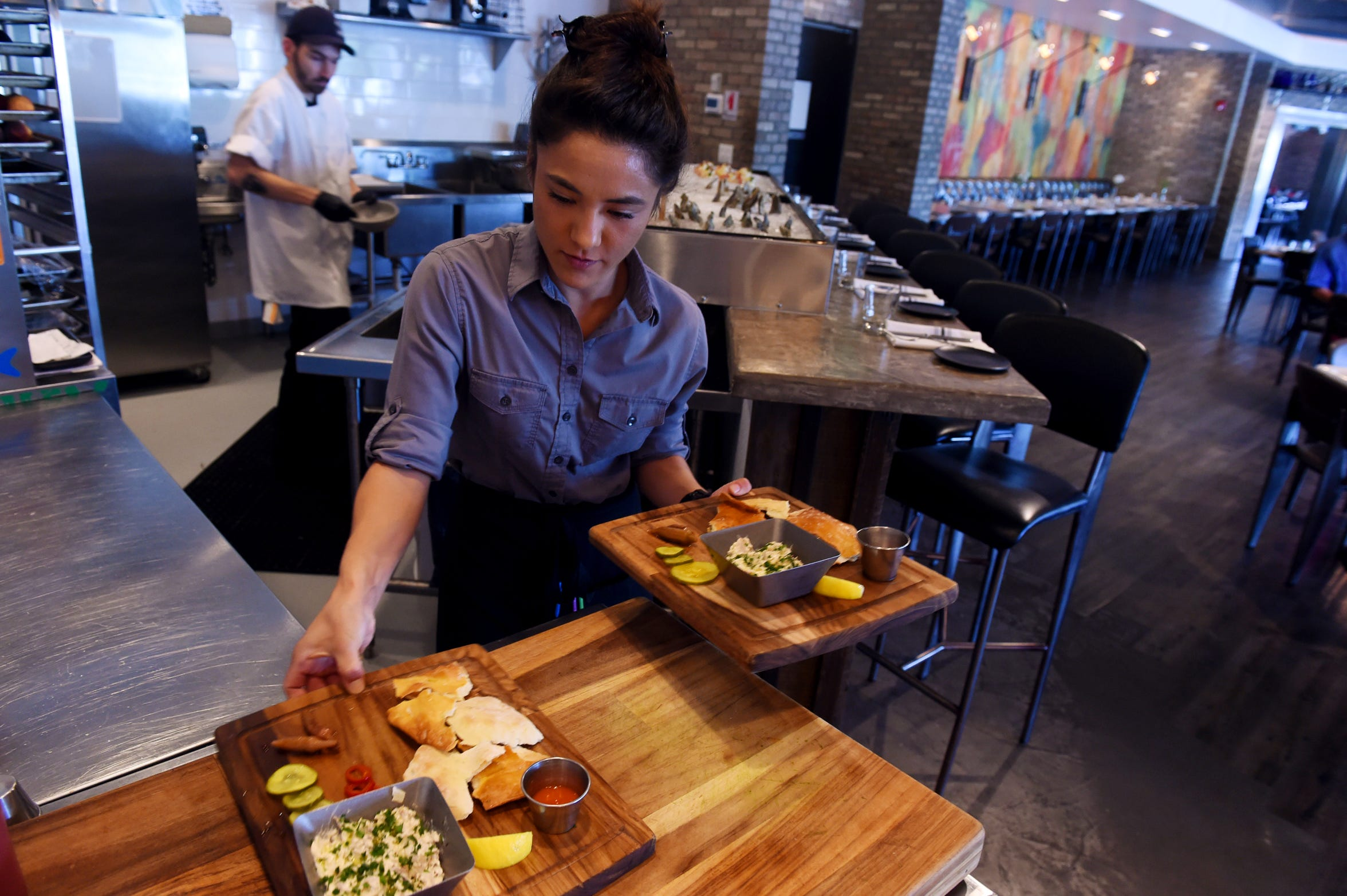 Server Sarah Ford prepares to serve up two boards of smoked cobia dip at the start of the dinner rush at District Table & Bar in Port Salerno. The board consists of smoked cobia dip, pickles, fermented hot sauce, crackers, preserved lemon and herbs.