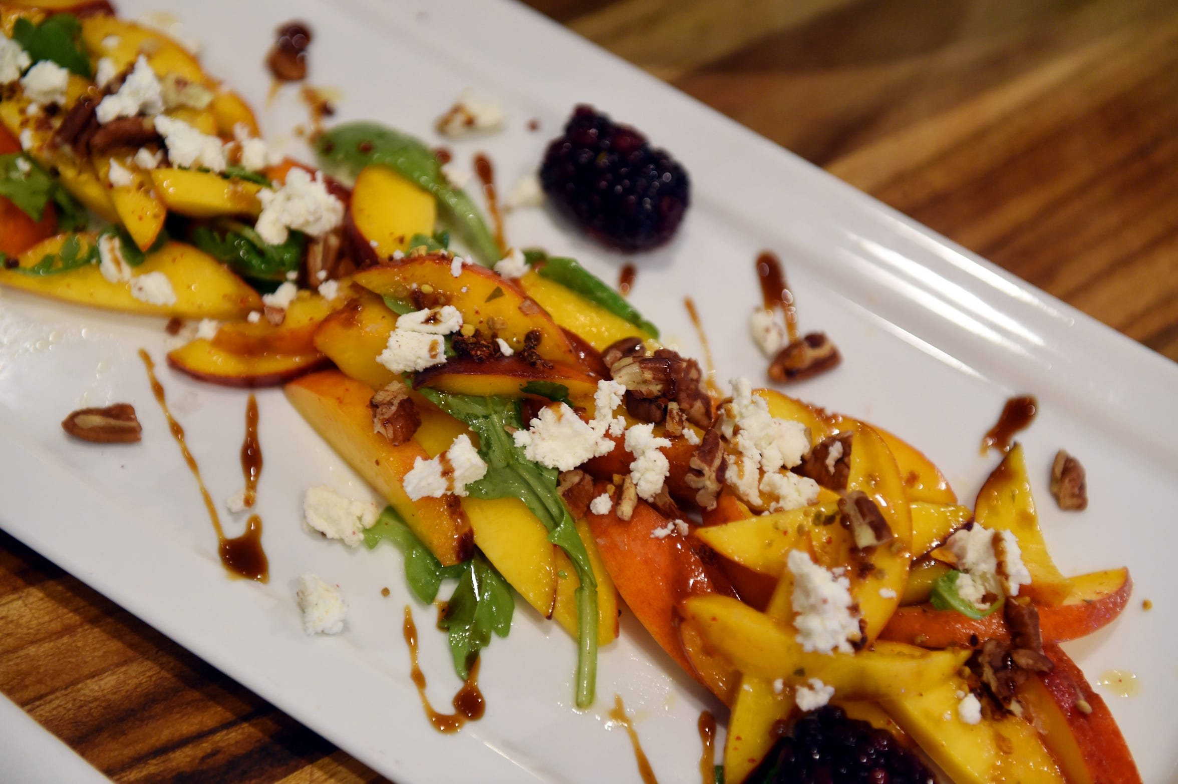 The Georgia peach salad consisting of chevre, arugula, honey vinaigrette, pecans, pink peppercorn pomegranate molasses, pickled blackberry and bee pollen at District Table & Bar in Port Salerno.