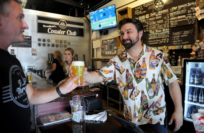 Tim Kazules, founder of Five Threads Brewing Company in Westlake Village, serves his friend Rusty Starnes a beer.  The brewery is celebrating its third anniversary in October and taking part in the Ventura County Star's Wine & Food Experience on Nov. 10.
